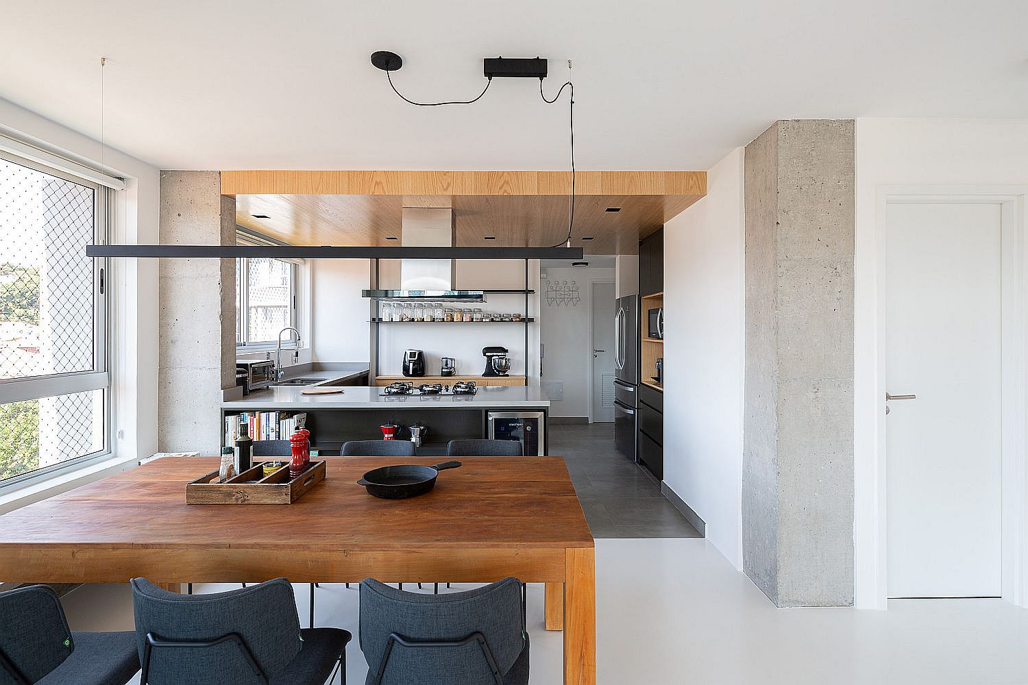 Wooden ceiling and a change in floor delineates the kitchen from the living area and dining space