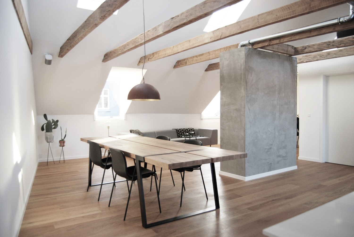 Wooden ceiling beams and concrete wall section in the dining area of the apartment