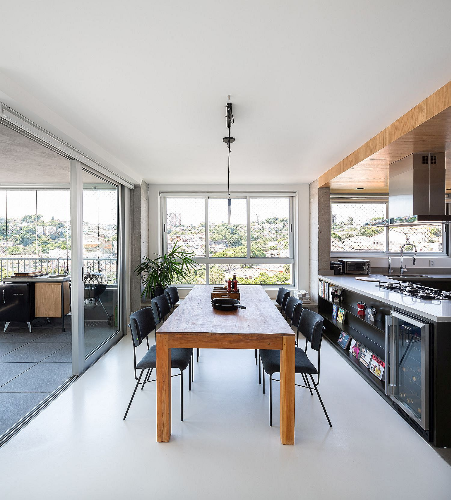 Wooden dining table sits between the kitchen on one side and the enclosed balcony on the other