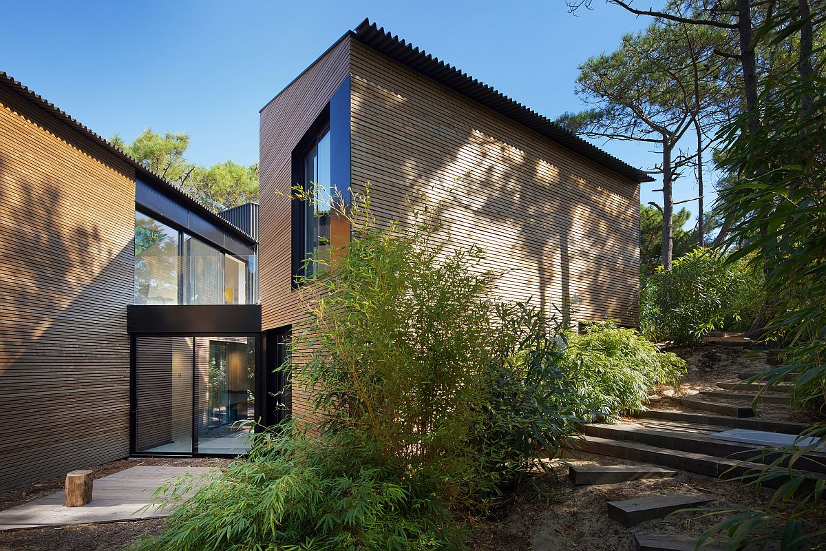 Wooden exterior of the house along with large glass walls and sliding doors adds modernity to the holiday home