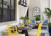 Beautiful-chairs-in-yellow-and-rug-in-blue-bring-color-to-this-modern-industrial-porch-dining-space-56909-217x155