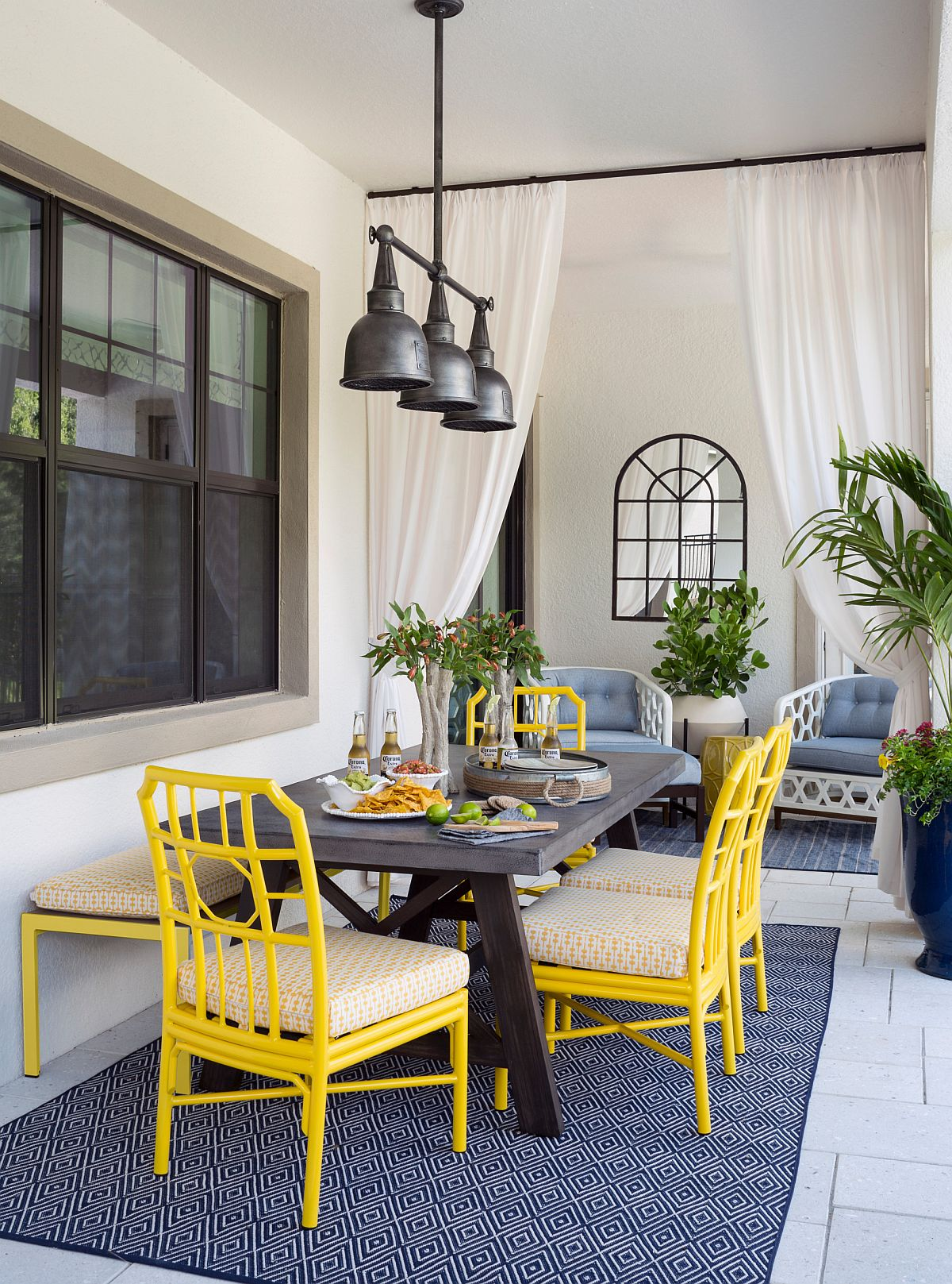 Beautiful-chairs-in-yellow-and-rug-in-blue-bring-color-to-this-modern-industrial-porch-dining-space-56909