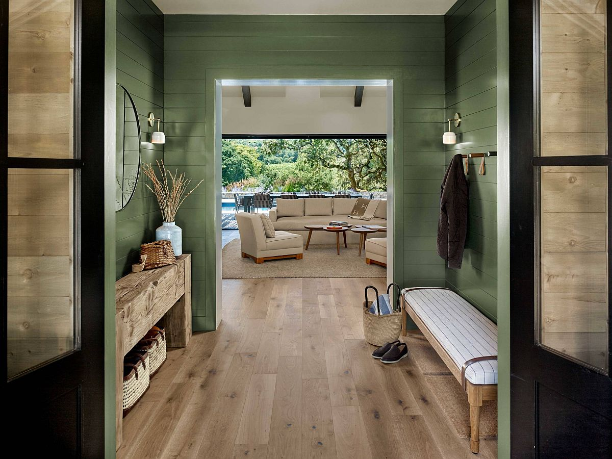 Beautiful farmhouse style entry in green also gives a glimpse of the living area and the rear garden