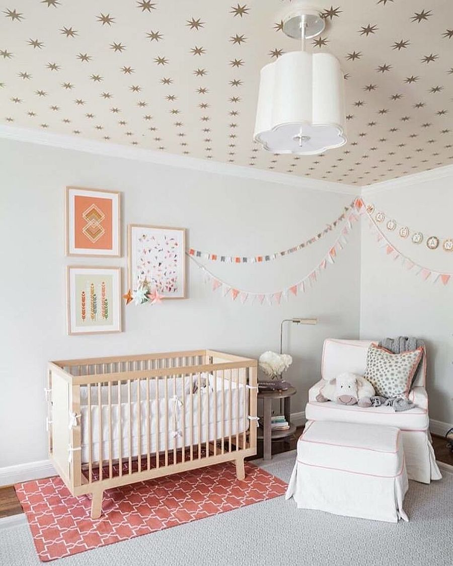 Classy nursery in white and pink with wallpapered ceiling and a relaxing ambiance