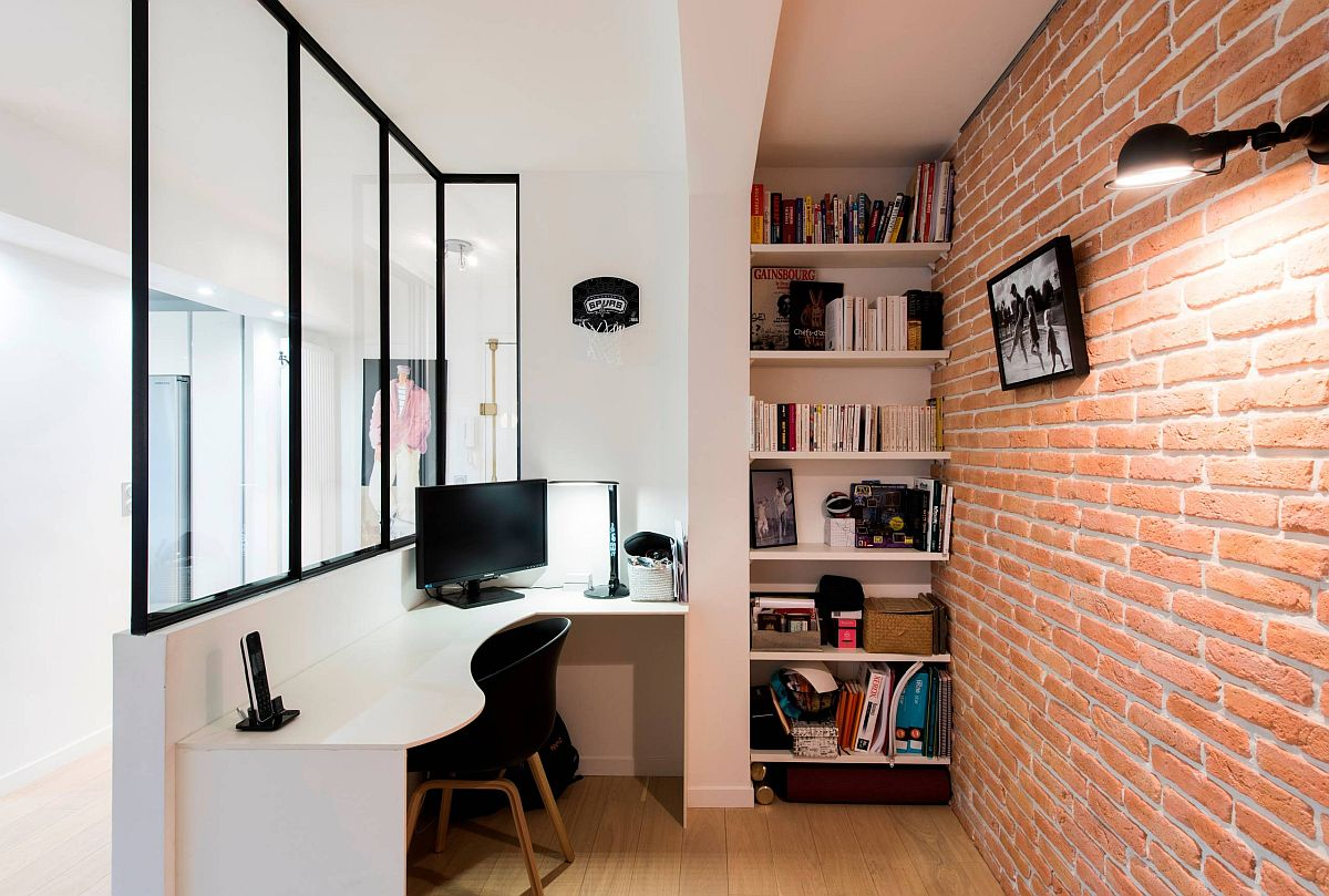 Curvy desk and exposed brick wall make an impact in this small home office