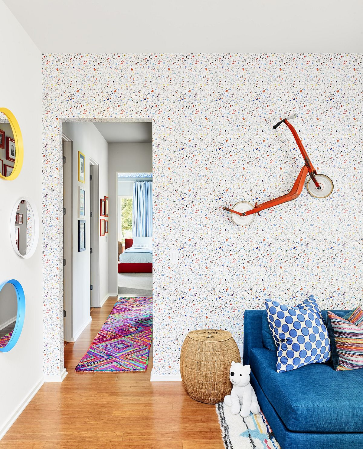 Custom wallpaper and little scooter on the wall bring eclectic charm to this lovely little room