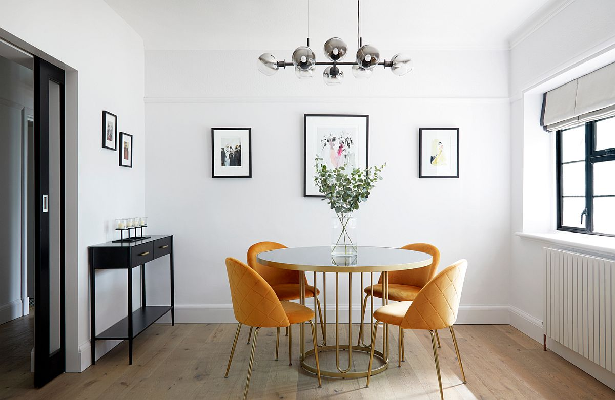 Delightful modern dining room with round white and gold dining table and four yellow chairs