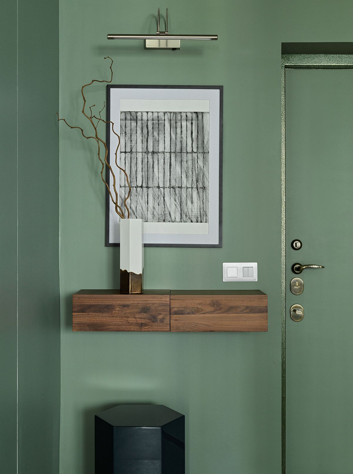 Entry of small Moscow apartment with green walls and a green door along with a floating wooden console that is minimal
