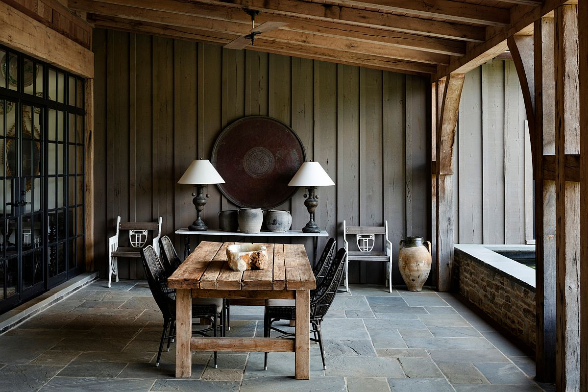 Farmhouse-style-covered-porch-with-heavy-wooden-dining-table-and-lovely-dark-chairs-71071