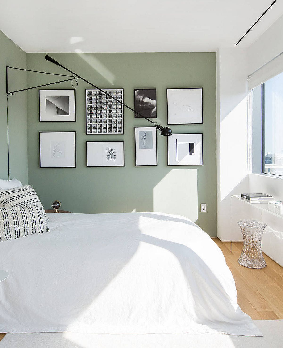 Gallery wall with black and white photographs set against a pastel green wall steals the show in this bedroom of New York home