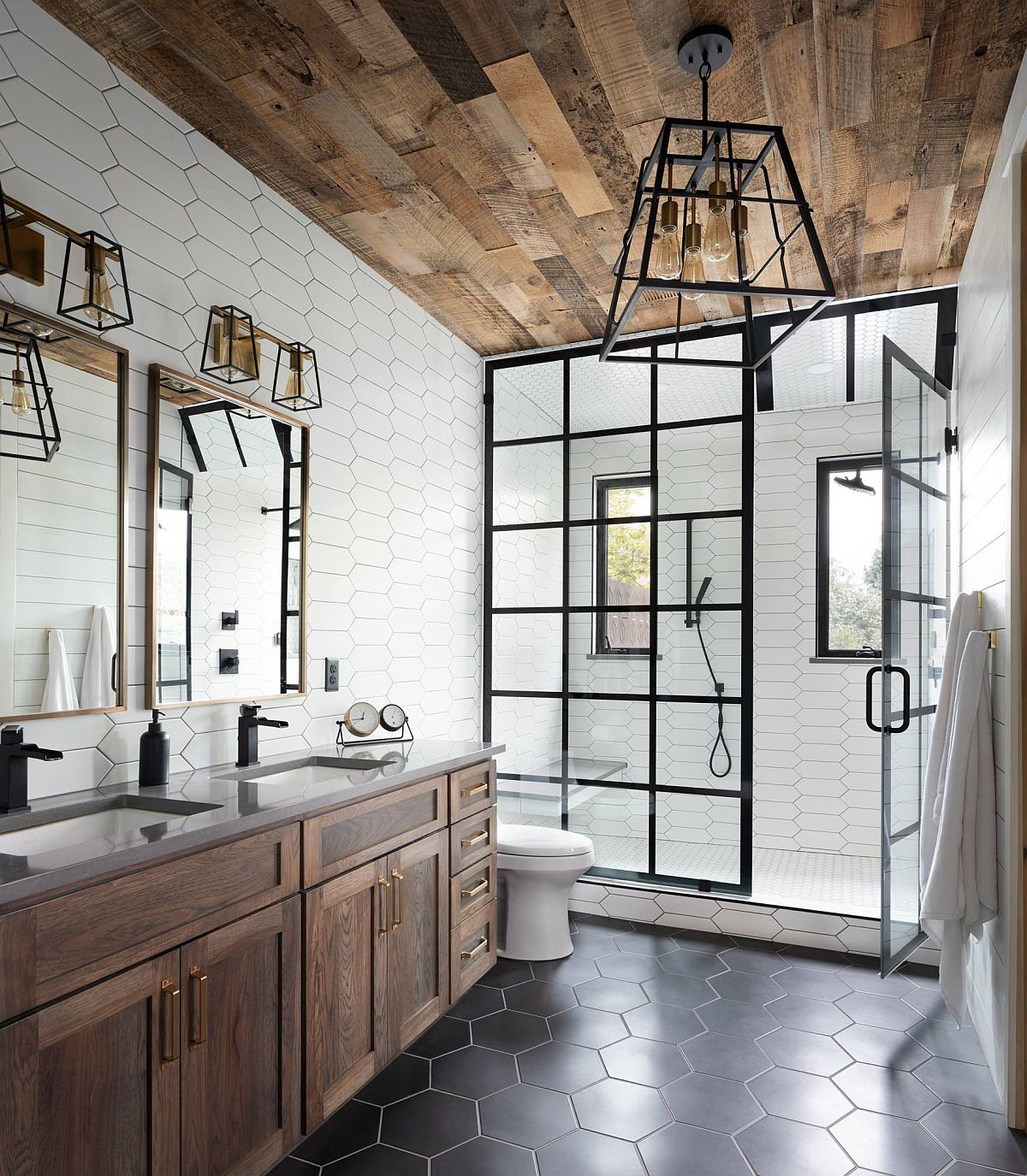 Gorgeous industrial farmhouse style bathroom with hexagonal gray floor tiles. wooden ceiling and lovely dark-framed shower area