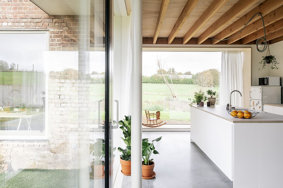 Gorgeous modern white and wood kitchen with a view of the fields all around