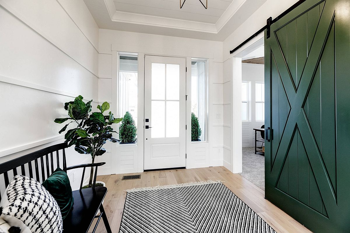 Indoor plant combined with large sliding barn door in green add color to this fabulous white entry