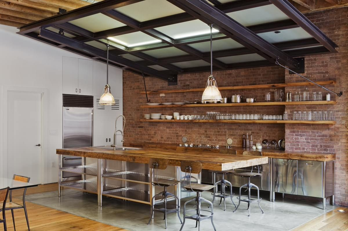 Industrial-farmhouse style kitchen with exposed brick wall backdrop and sleek wooden floating shelves