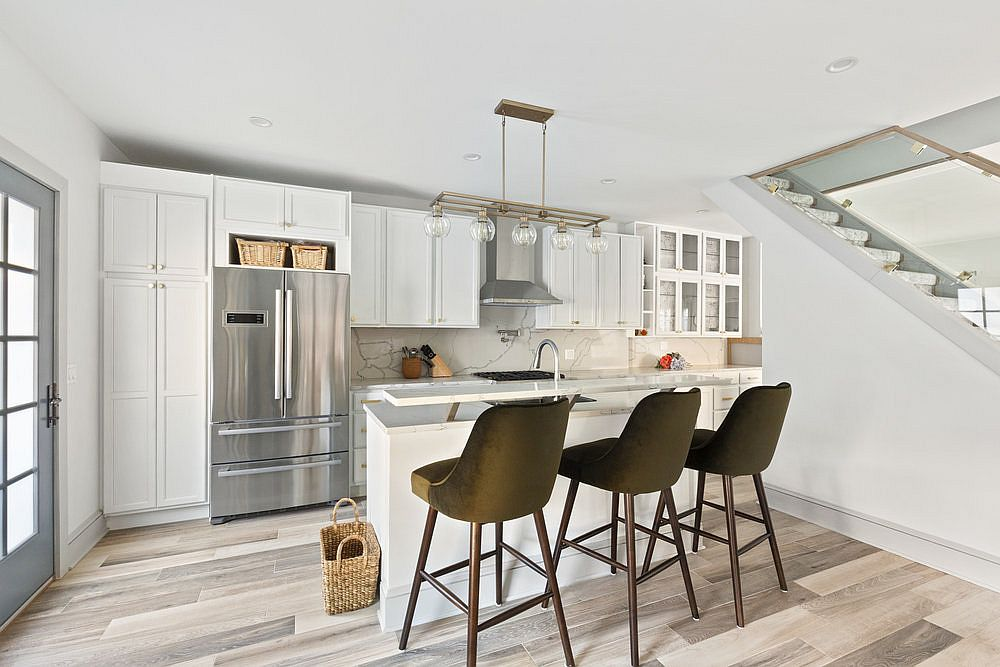 Kitchen of the renovated townhouse in white with wooden floor and stone backsplash