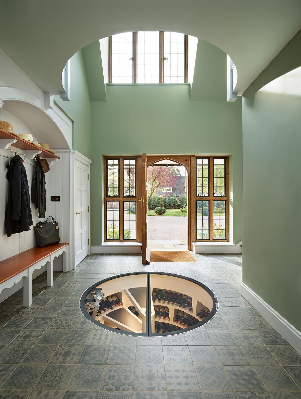 Large entry in lovely green with modern style and ample natural light also offers a window into the wine cellar