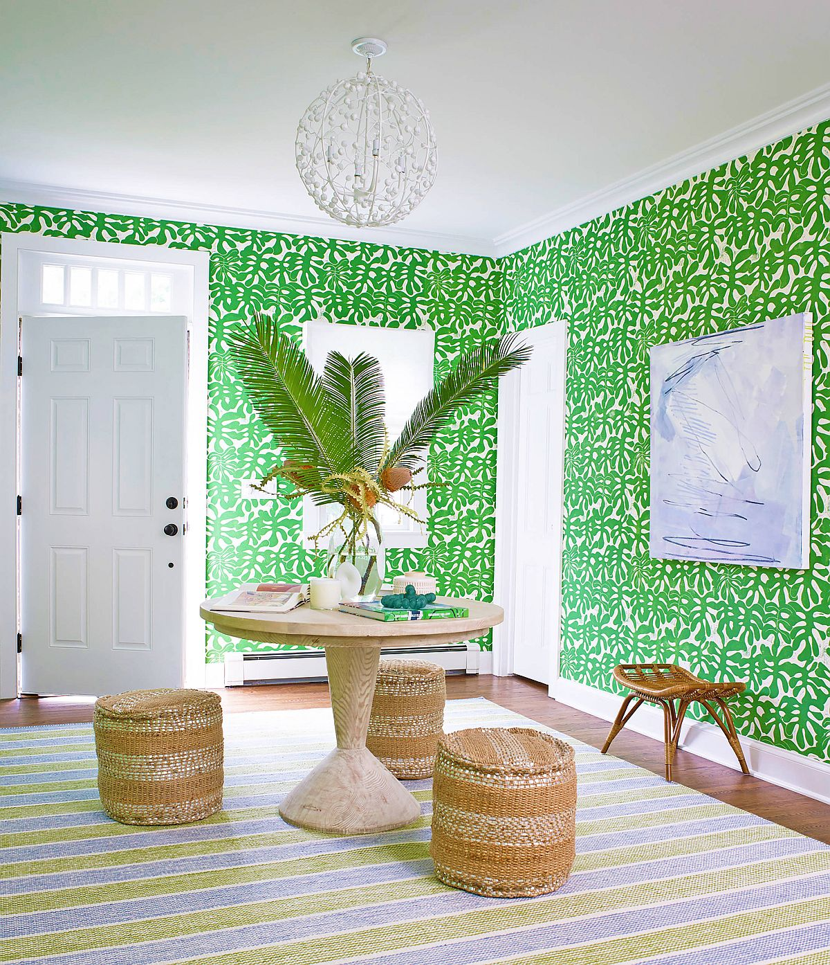 Lovely wallpaper in green adds color to the entryway along with beautiful striped rug