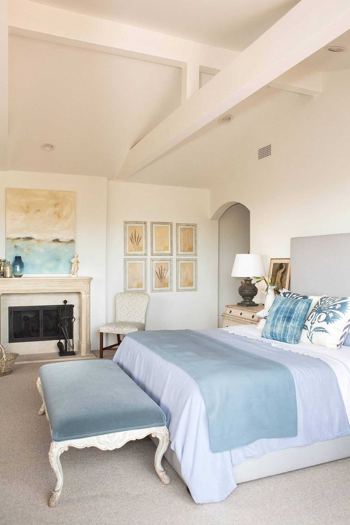 Luxurious master bedroom of Malibu beach house in white and blue with an elegant gallery wall