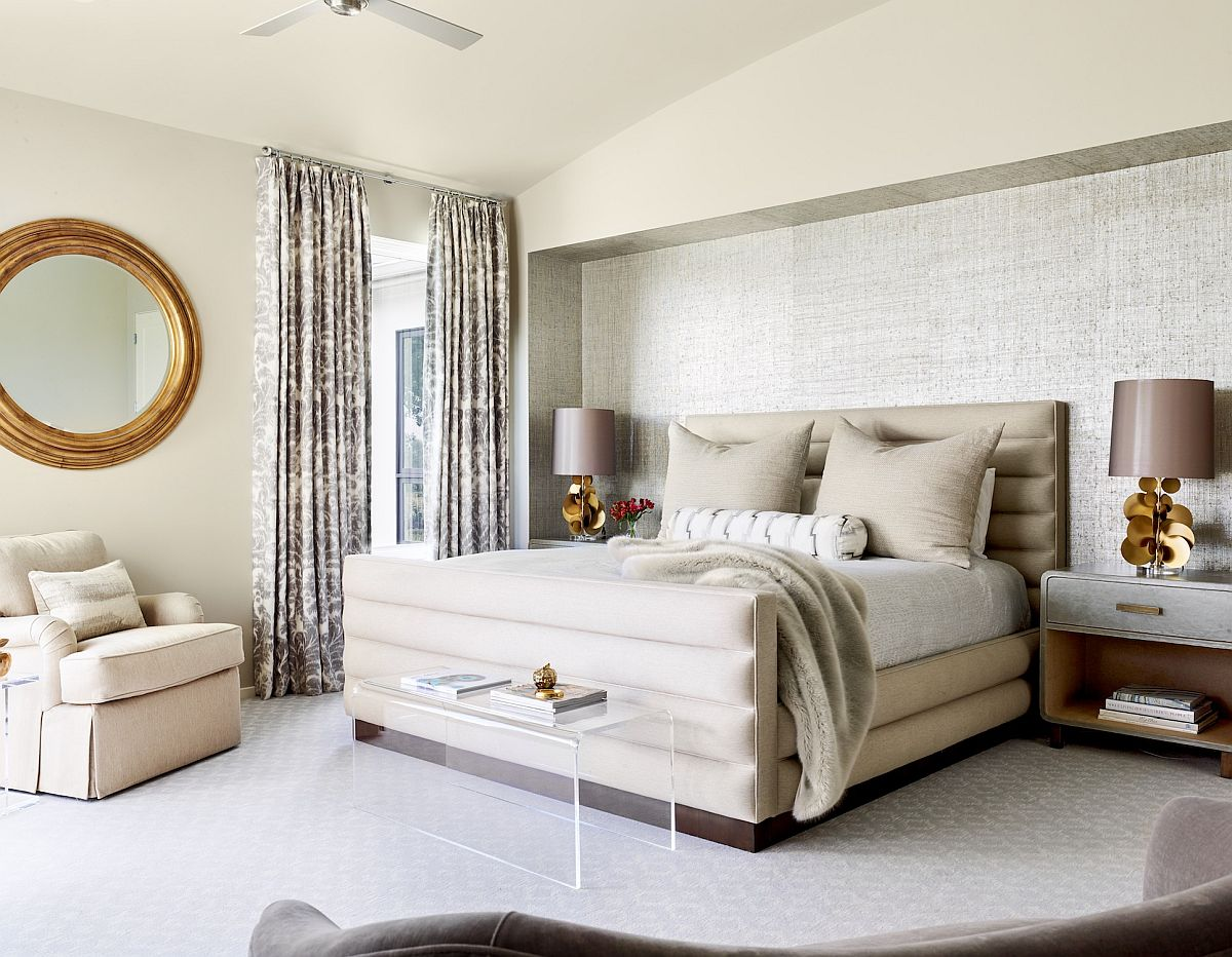Master bedroom in white where the bedside table lamps bring symmetry to the large space