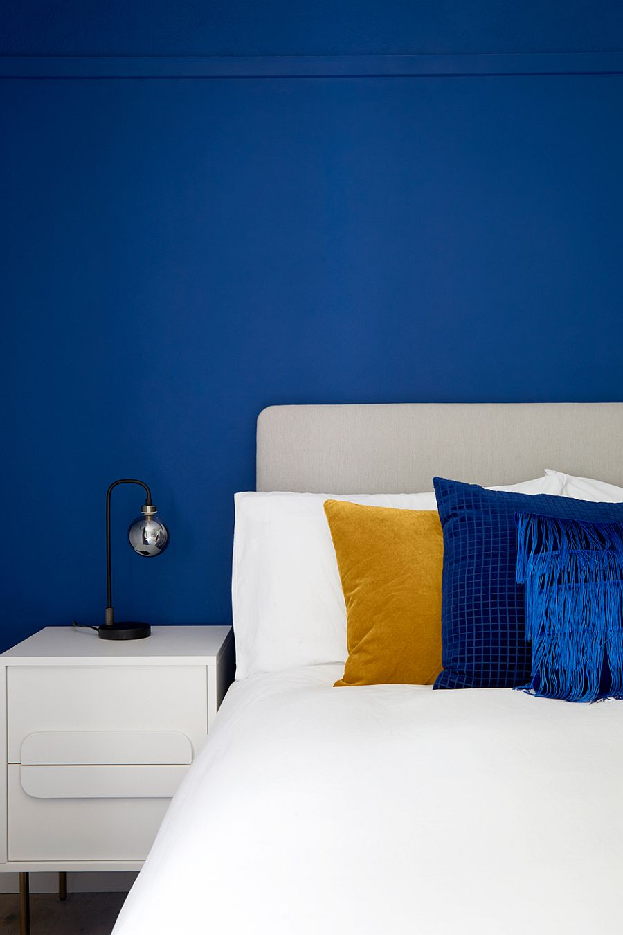 Modern and minimal bedside table lamp in a bedroom filled with plenty of blue