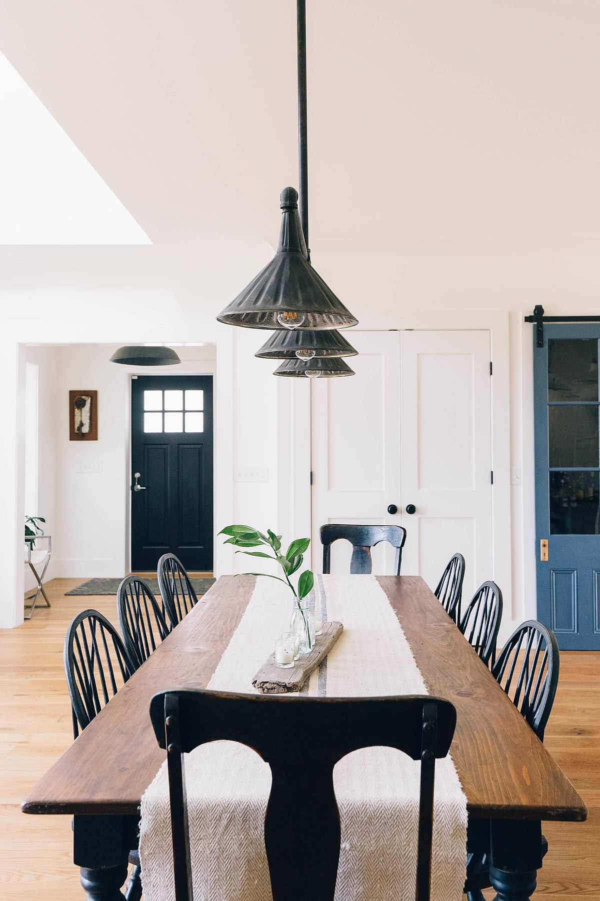Pendant light and large wooden table brig industrial and farmhouse touches to this dining area