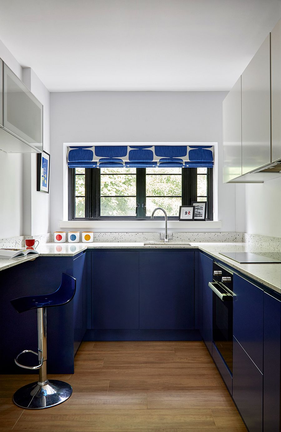 Polished contemporary kitchen in white and blue with blue cabinets below and white cabinets above