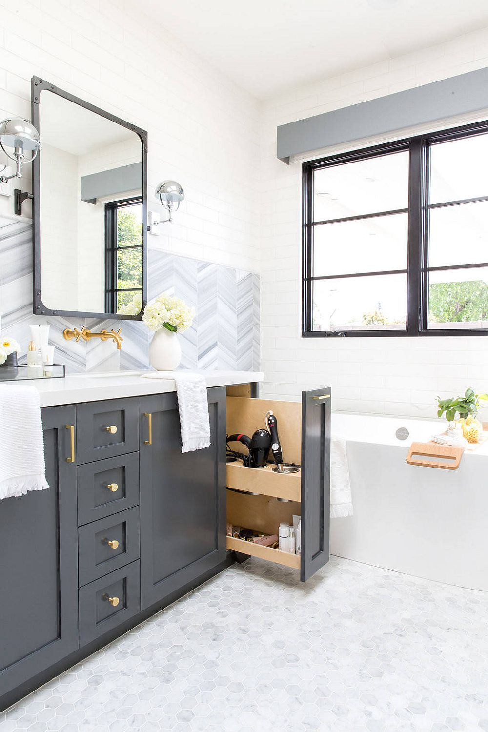 Polished industrial-farmhouse bathroom in white with gray cabinets and ample natural light