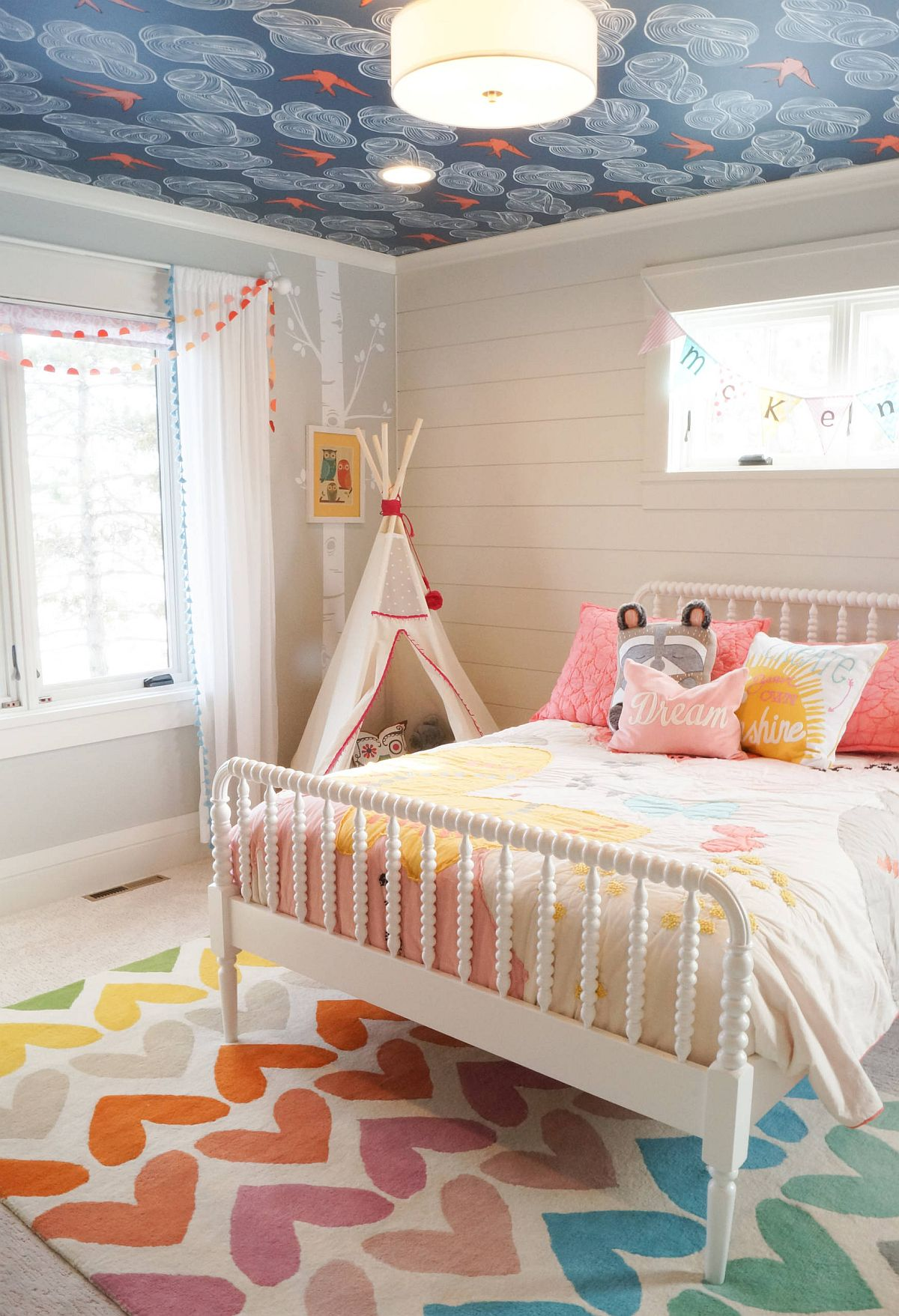 Popular wallpaper makes its way on to the ceiling in this kids' room even as the rug adds more color