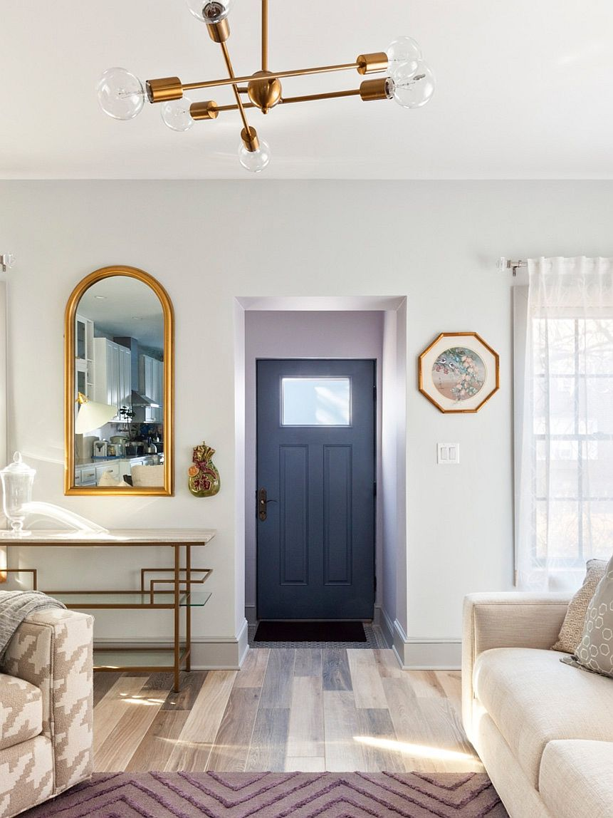 Remodeled interior of the townhouse in New York with a bluish-gray door and a white backdrop