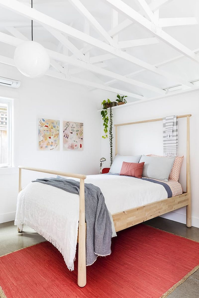 Small bedroom in white with pops of bright pink and red along with an open-vaulted ceiling