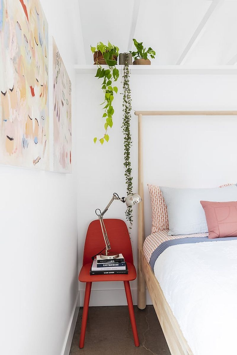 Small red chair used as bedside table in the modest vacation home bedroom
