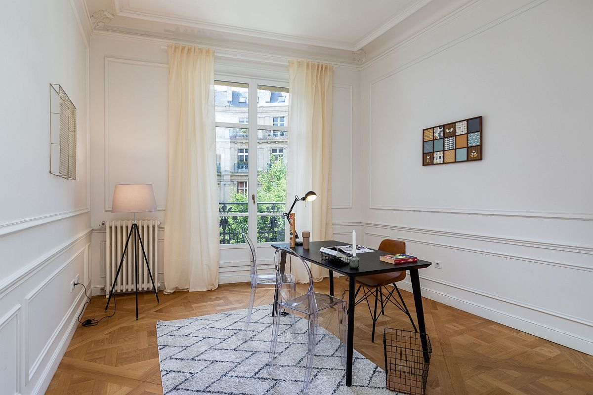 Spacious and contemporary home office in Paris with freestanding desk and acrylic chairs