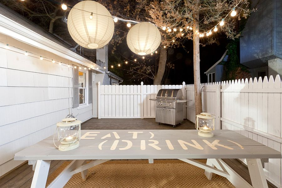 String and lantern lighting turn this small wooden deck into a beach style hangout for staycation