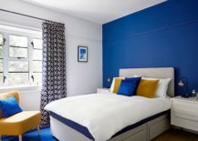 Stunning blue accent wall and rug for the modern bedroom in blue white and yellow 78489 217x155 - Black, White and Brilliant Pops of Yellow Revitalize Old Epsom Apartment