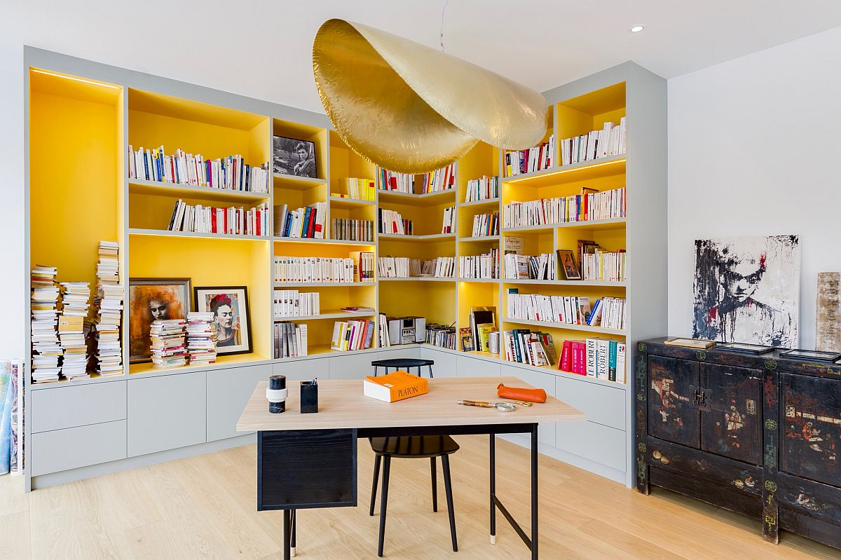Stunning pendant in gold along with fabulous yellow shelves enliven this home office