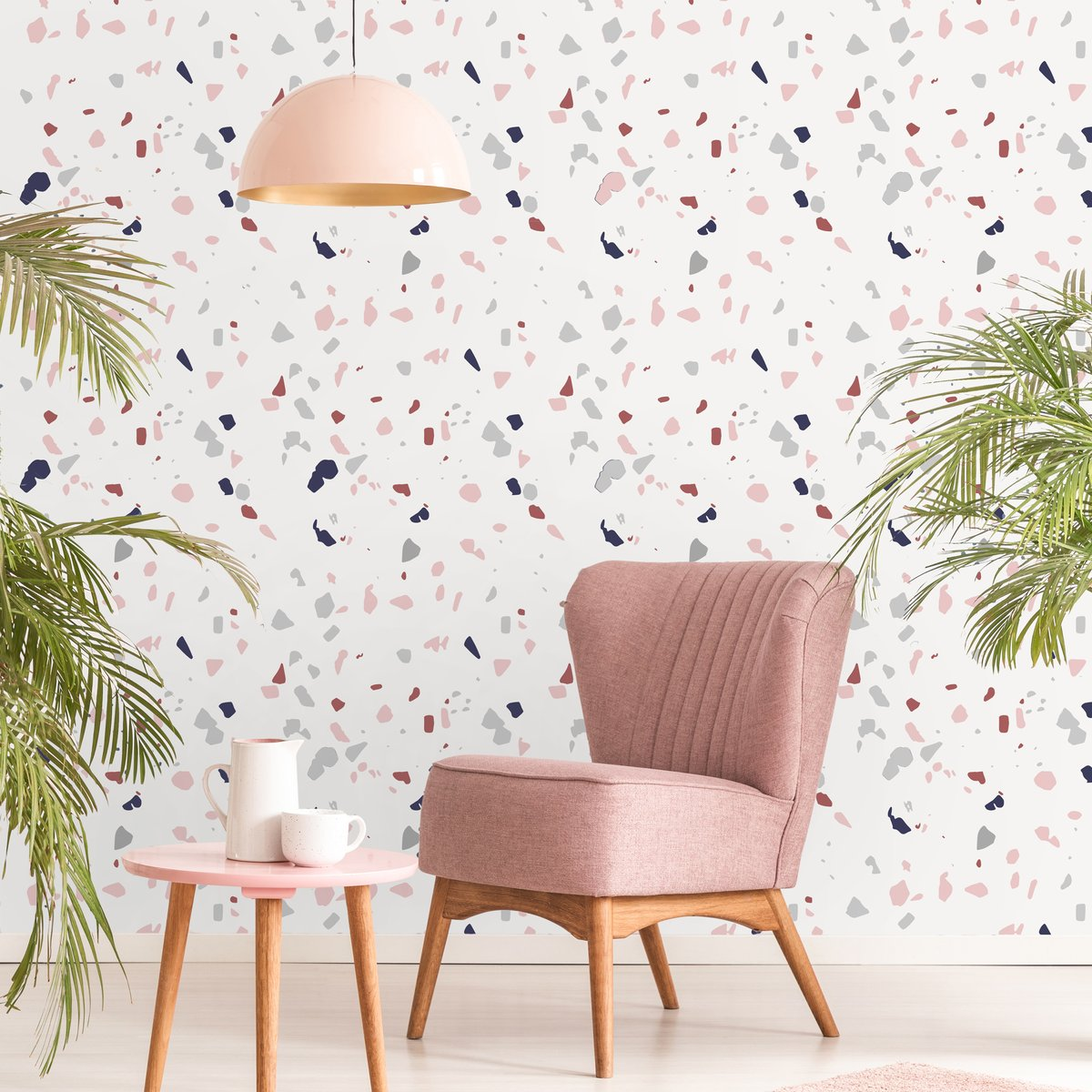 Pink lamp above wooden table and armchair in pastel living room interior with plants. Real photo