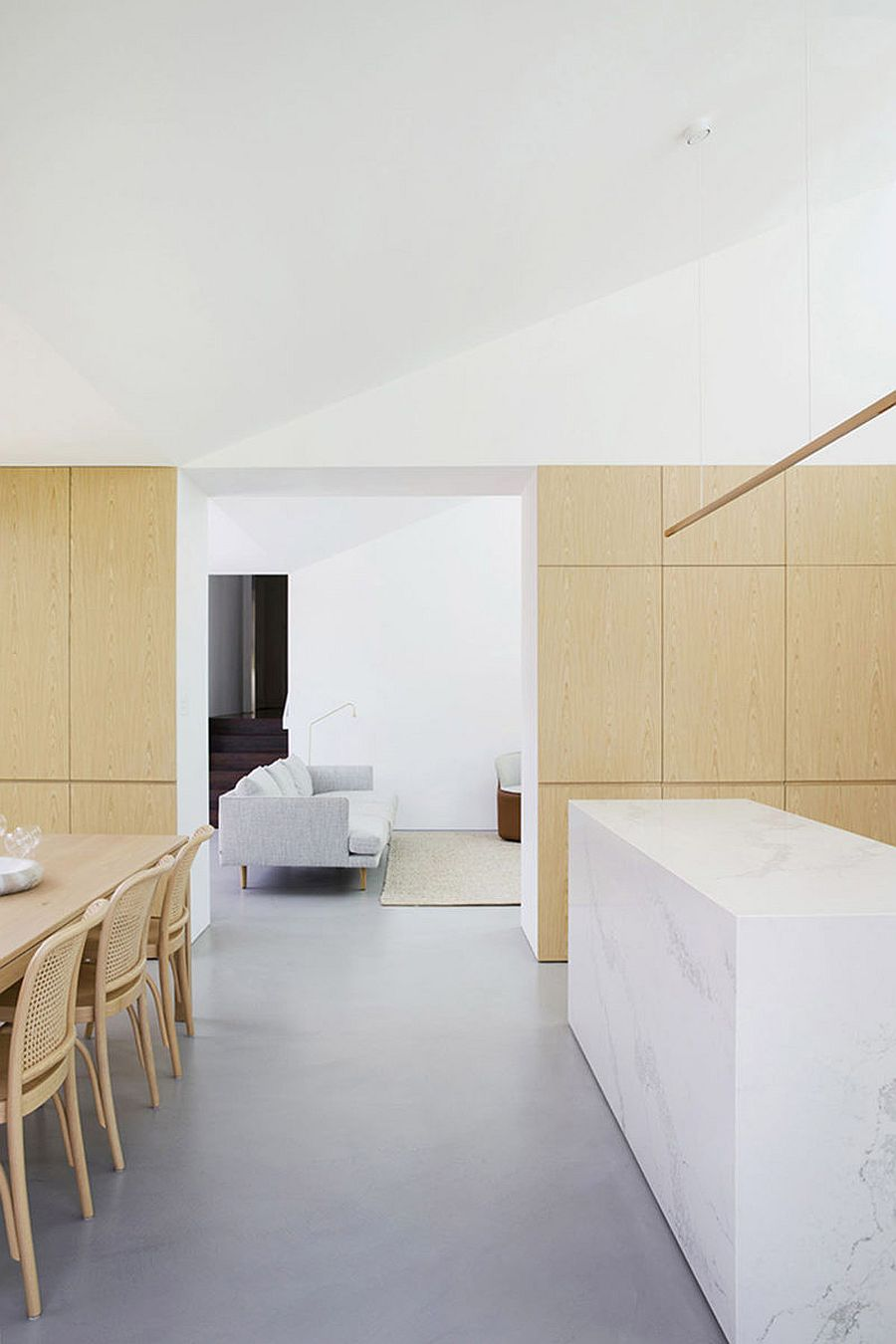 Wood-on-the-walls-and-the-dining-table-bring-contrast-and-warmth-to-the-clean-space-in-white-56388