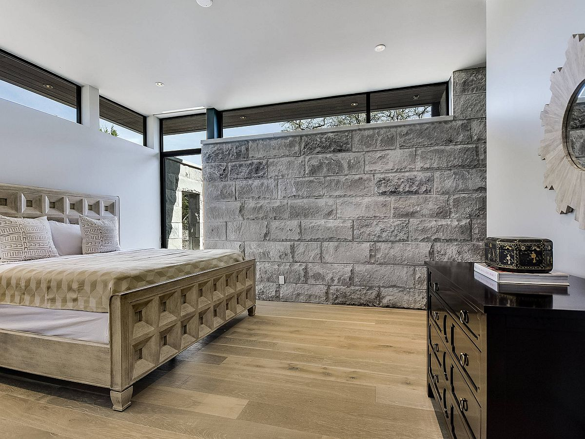 Amazing stone wall in the bedrooms ushers in gray in a space already filled with neutral colors