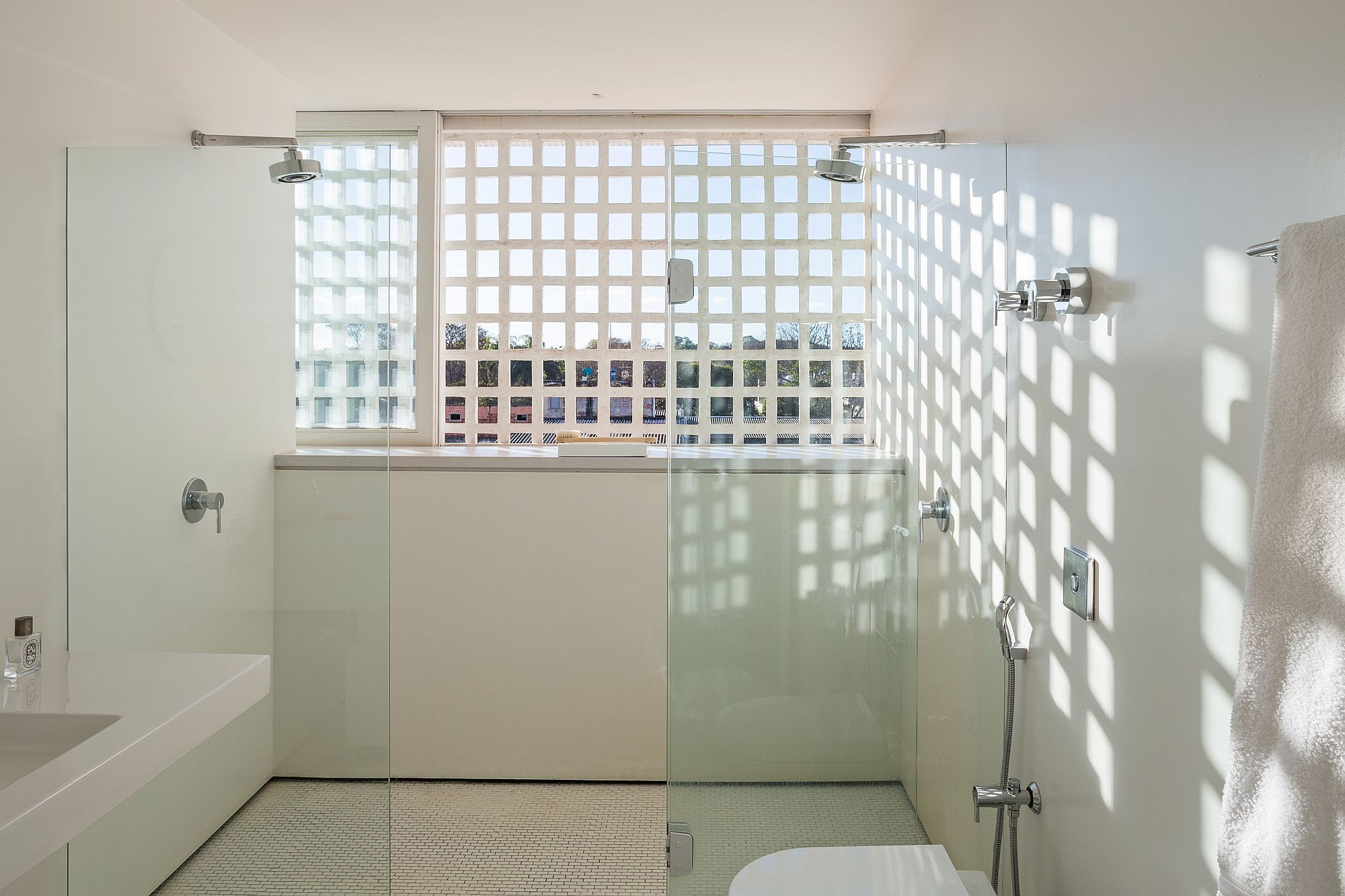 Bathroom in white with ample natural light and glass shower zone