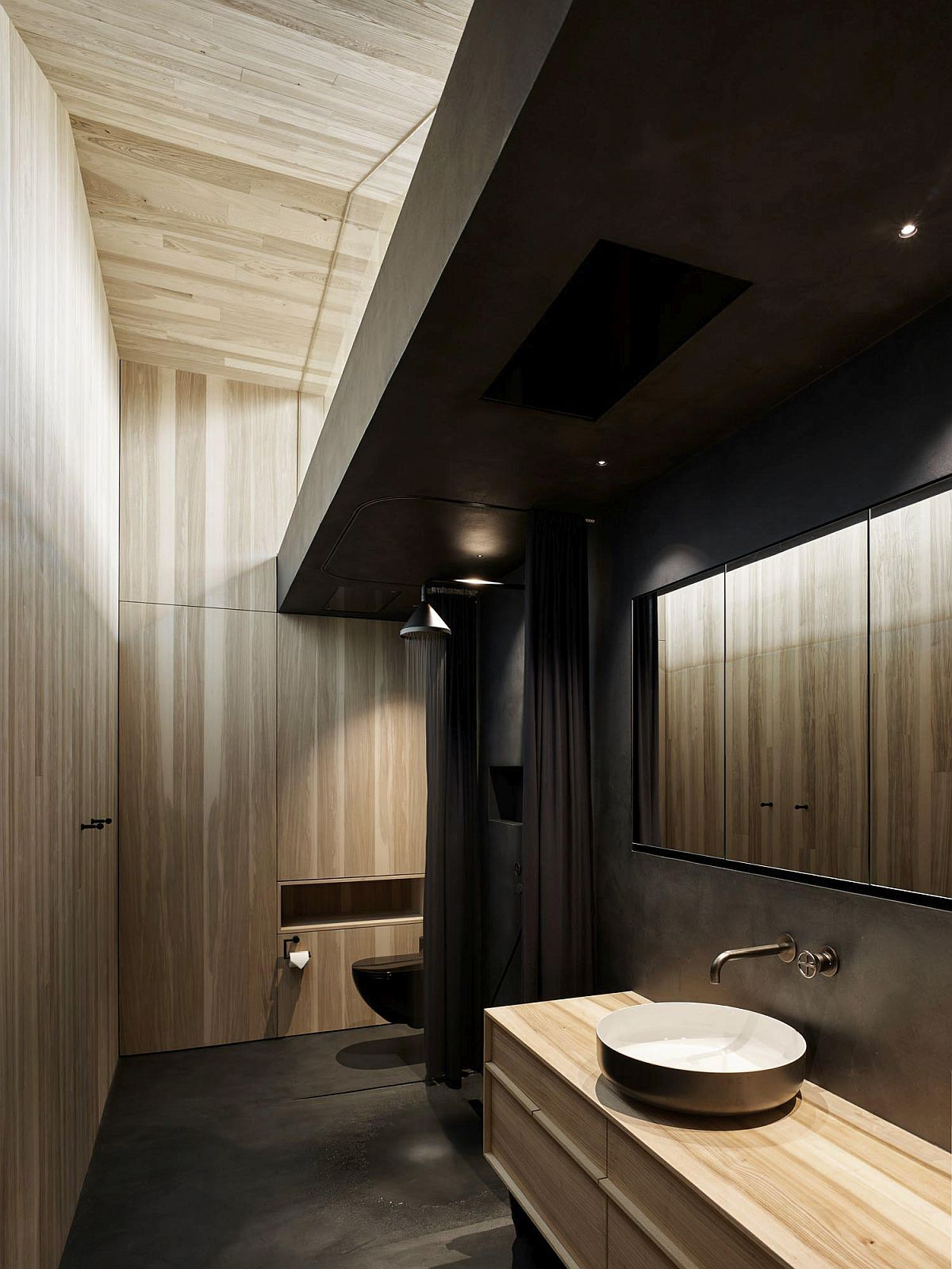 Bathroom of the house in wood and black moves away from the usual color palette