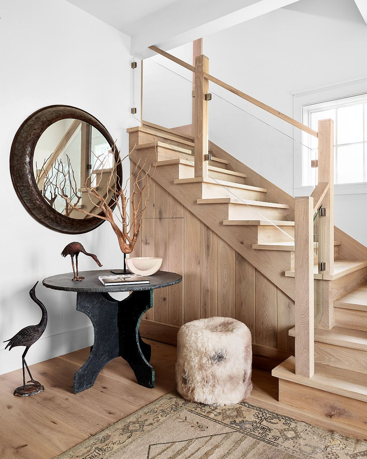 Beach style entry to the bungalow with a vintage console table, round mirror and staircase leading to the upper level