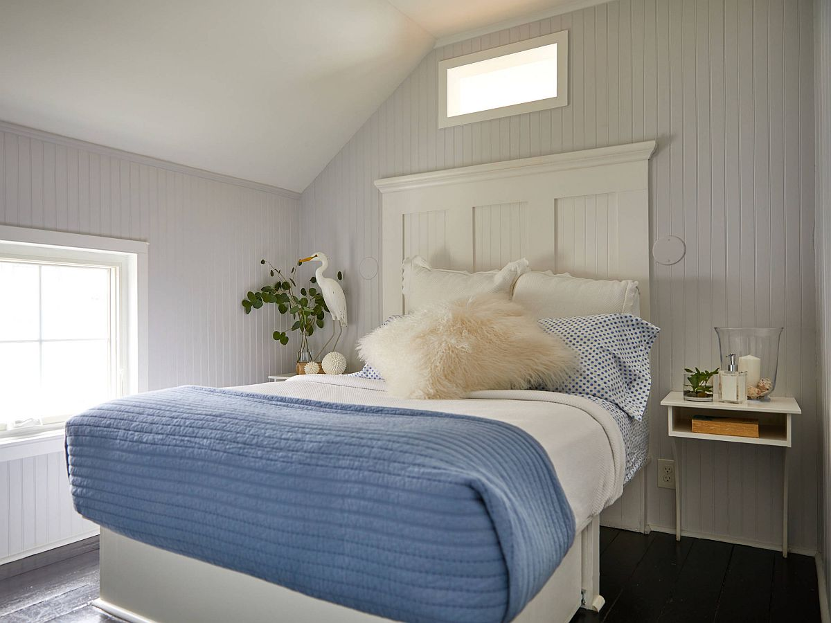 Black painted floor adds contrast to the modern coastal bedroom in white with blue bedding