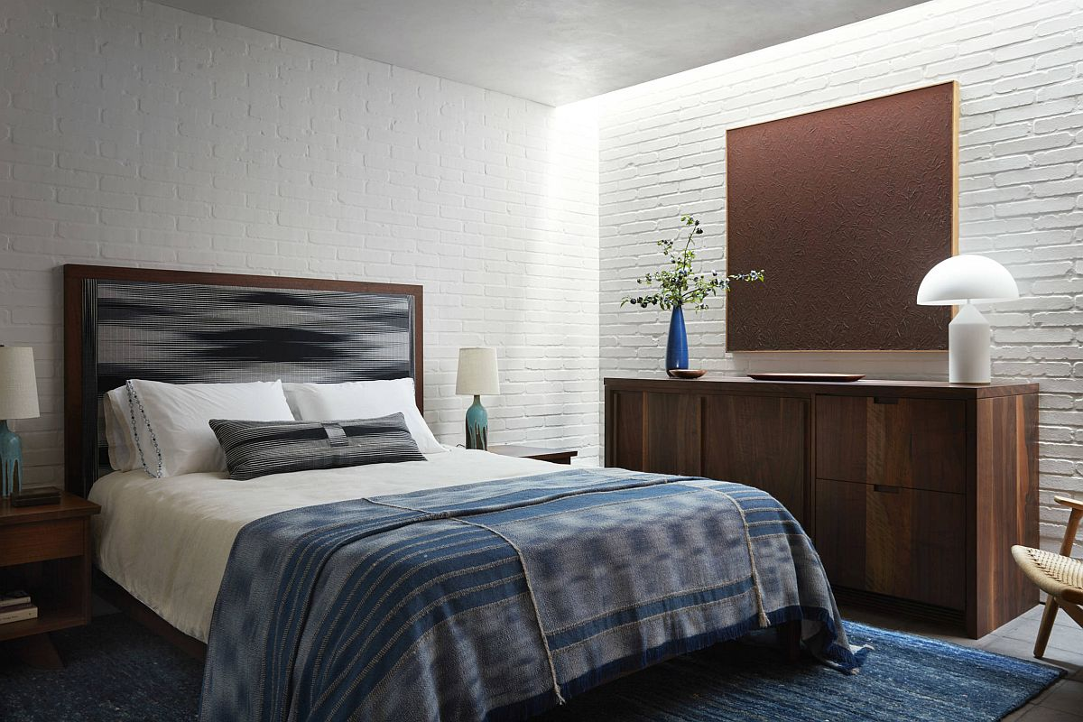 Blue accents, wooden decor and whitewashed brick walls create a cozy, relaxing bedroom