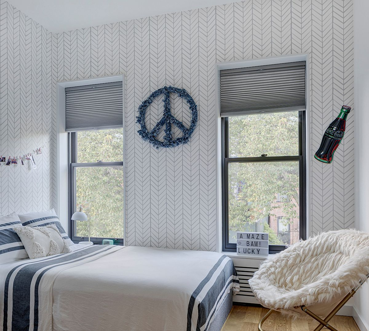 Blue and white teen bedroom that is gender neutral features pattern-filled walls