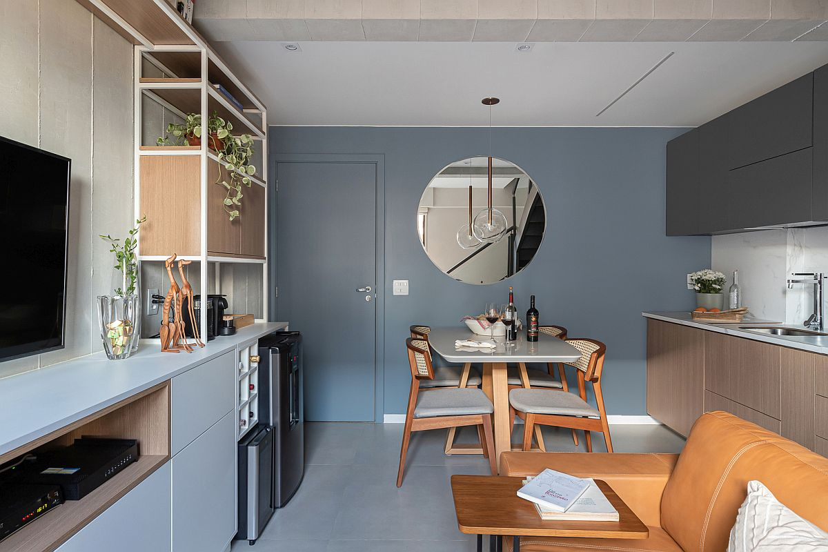 Blue, gray and wood shape the social zone and kitchen on the lower level of the duplex