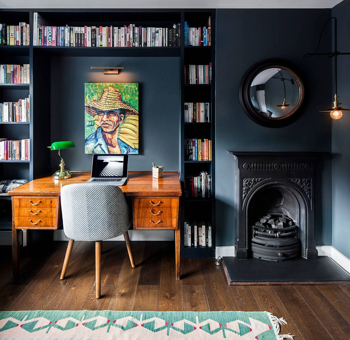 Bookshelves around the desk in the dark bluish-gray eclectic home office make an impact