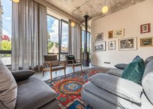 Brick-wall-that-is-painted-white-acts-as-gallery-wall-in-the-modern-industrial-living-room-with-a-lovely-colorful-rug-47867-217x155