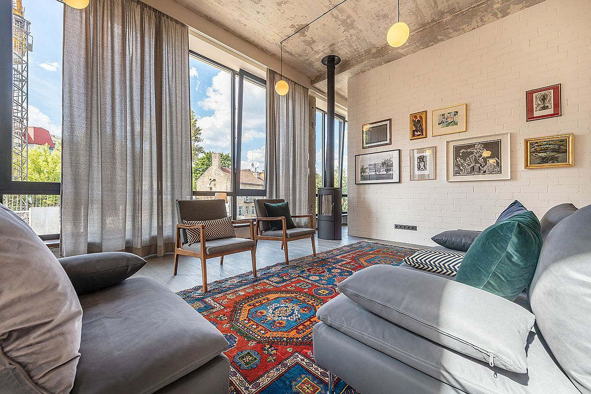 Brick-wall-that-is-painted-white-acts-as-gallery-wall-in-the-modern-industrial-living-room-with-a-lovely-colorful-rug-47867