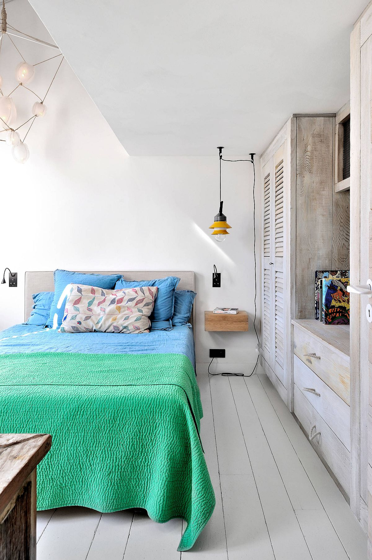 Brilliant use of colorful bedding brings life to this monochromatic bedroom in white