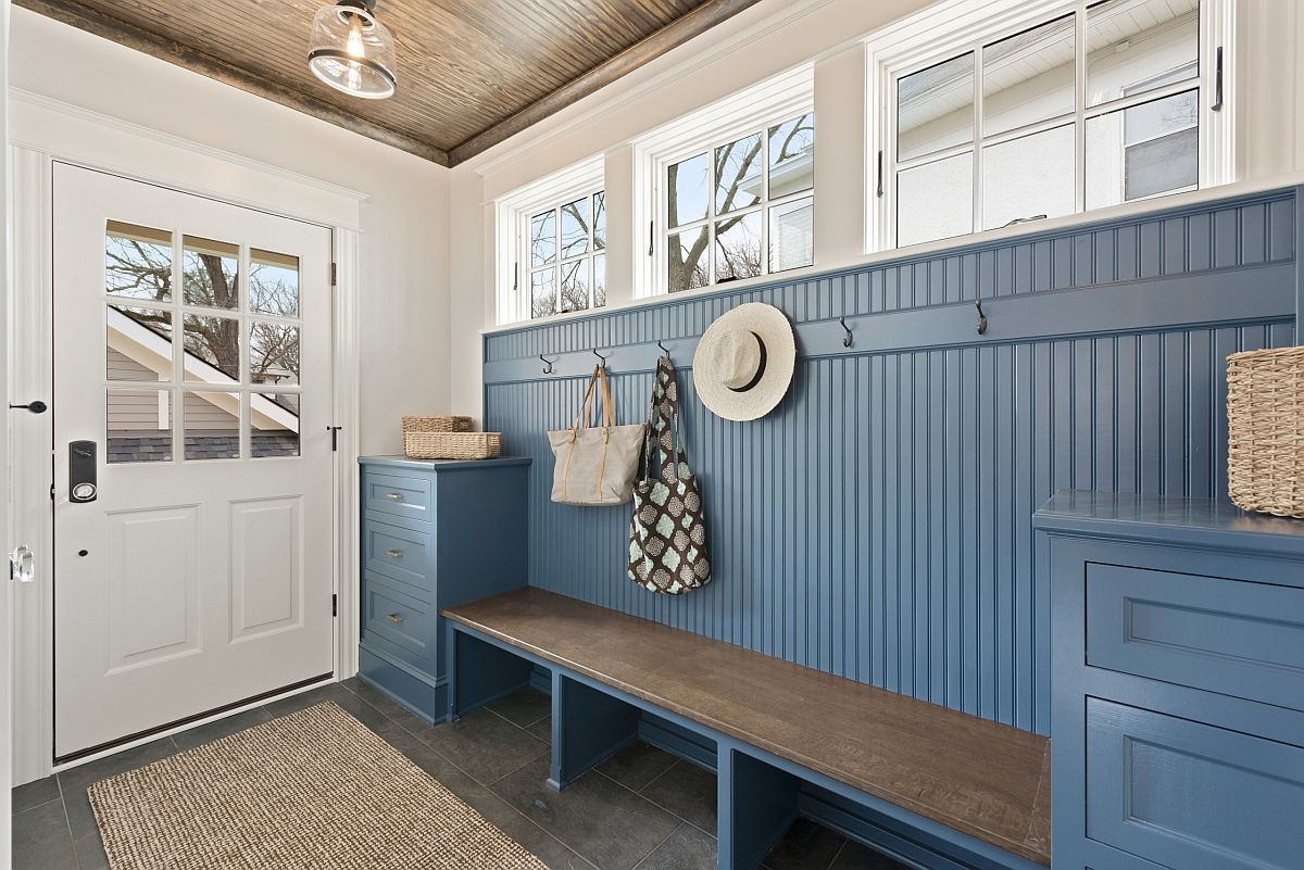 Cabinets in blue at both ends of the bench along with the wall in the backdrop add color to this white coastal mudroom